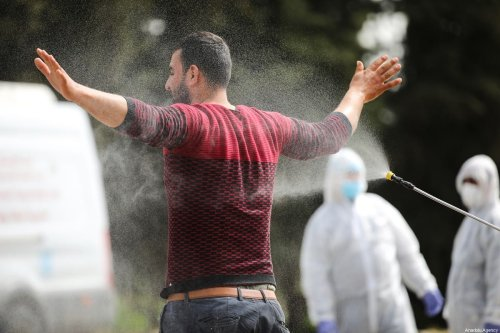 Workers spray disinfectant on Palestinian workers in Jerusalem, before they enter the West Bank through a checkpoint as part of precautions for the coronavirus (COVID-19) pandemic on 27 March 2020 [Mostafa Alkharouf/Anadolu Agency]