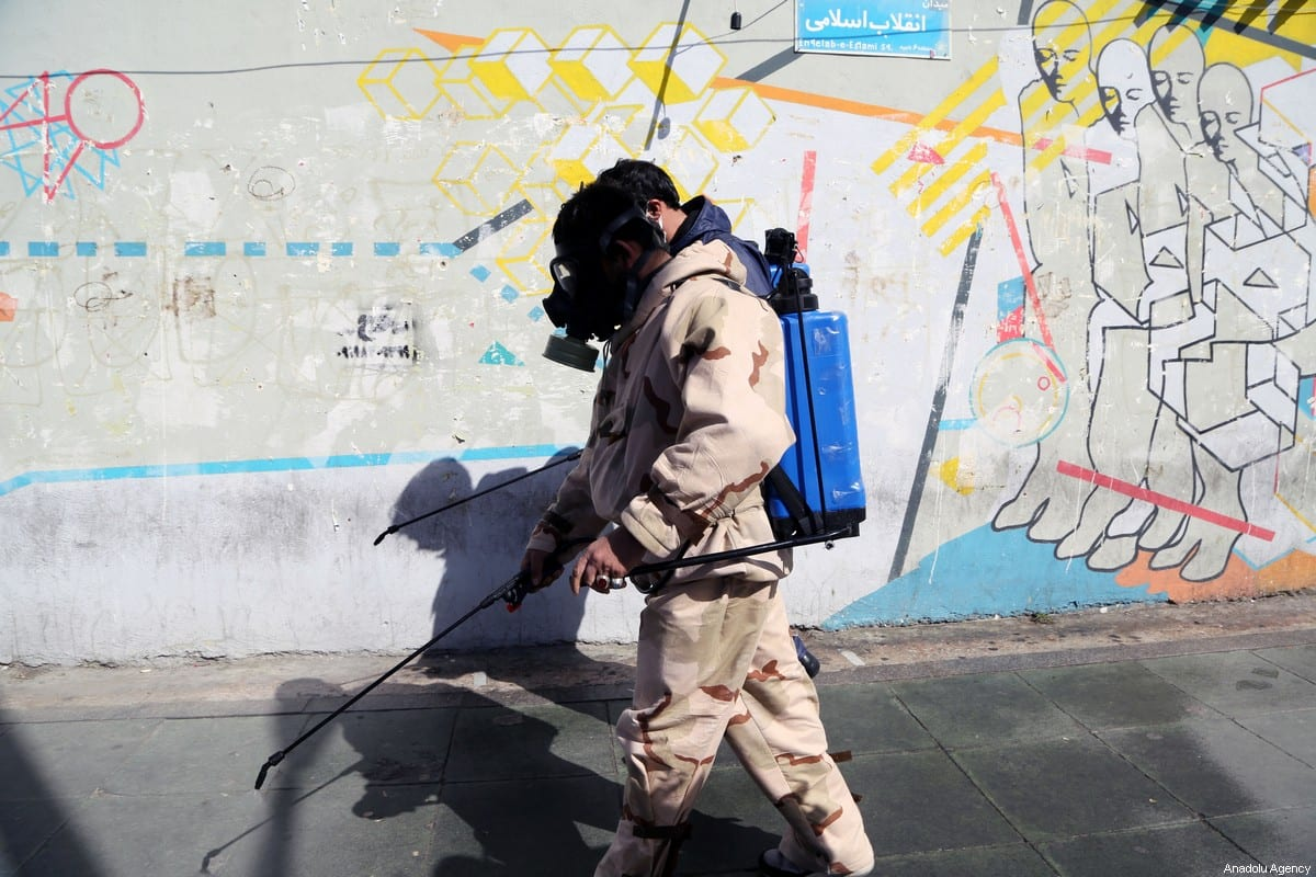 Fire brigade crew and Iran's Basij paramilitary forces, wearing protective suits, carry out disinfection works at streets as part of precautions against the coronavirus (COVID-19) pandemic in Tehran, Iran on 3 April 2020. [Fatemeh Bahrami - Anadolu Agency]