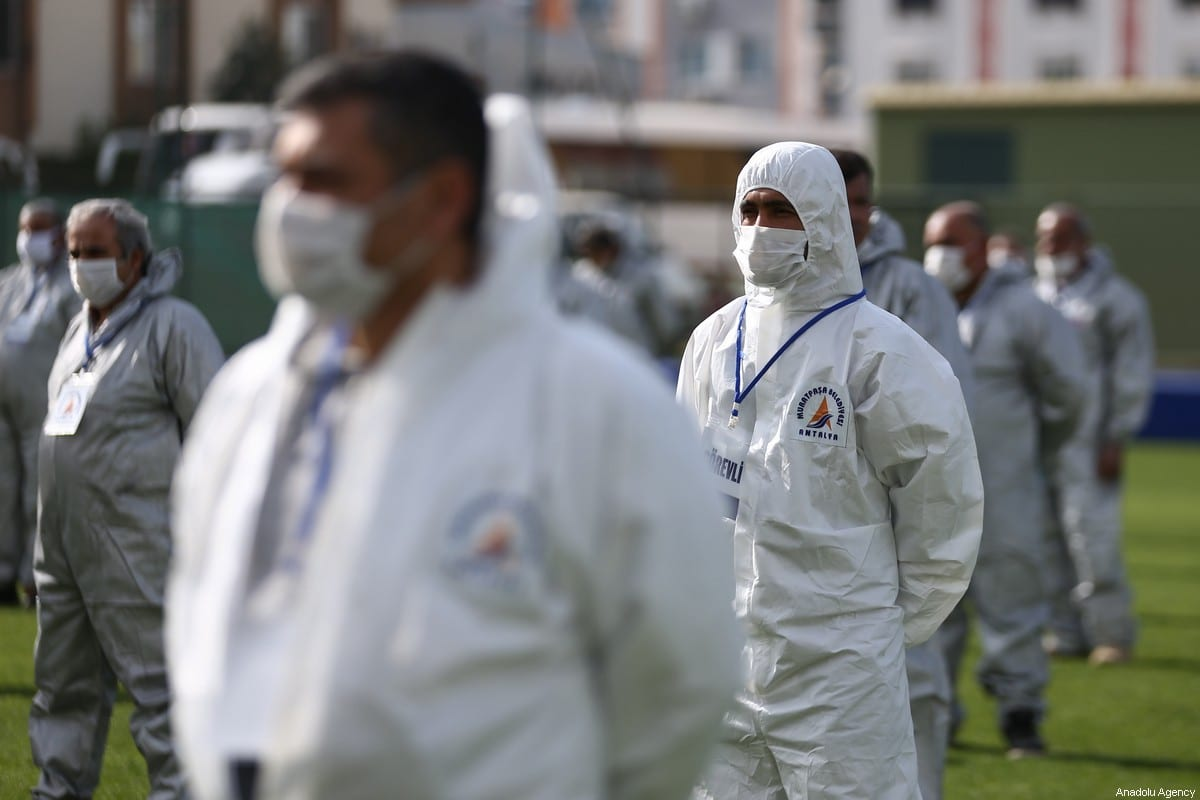 A crew, consisting of 120 people in special suits, receive masks that they will distribute in Antalya, Turkey on 4 April 2020 [Orhan Çiçek/Anadolu Agency]