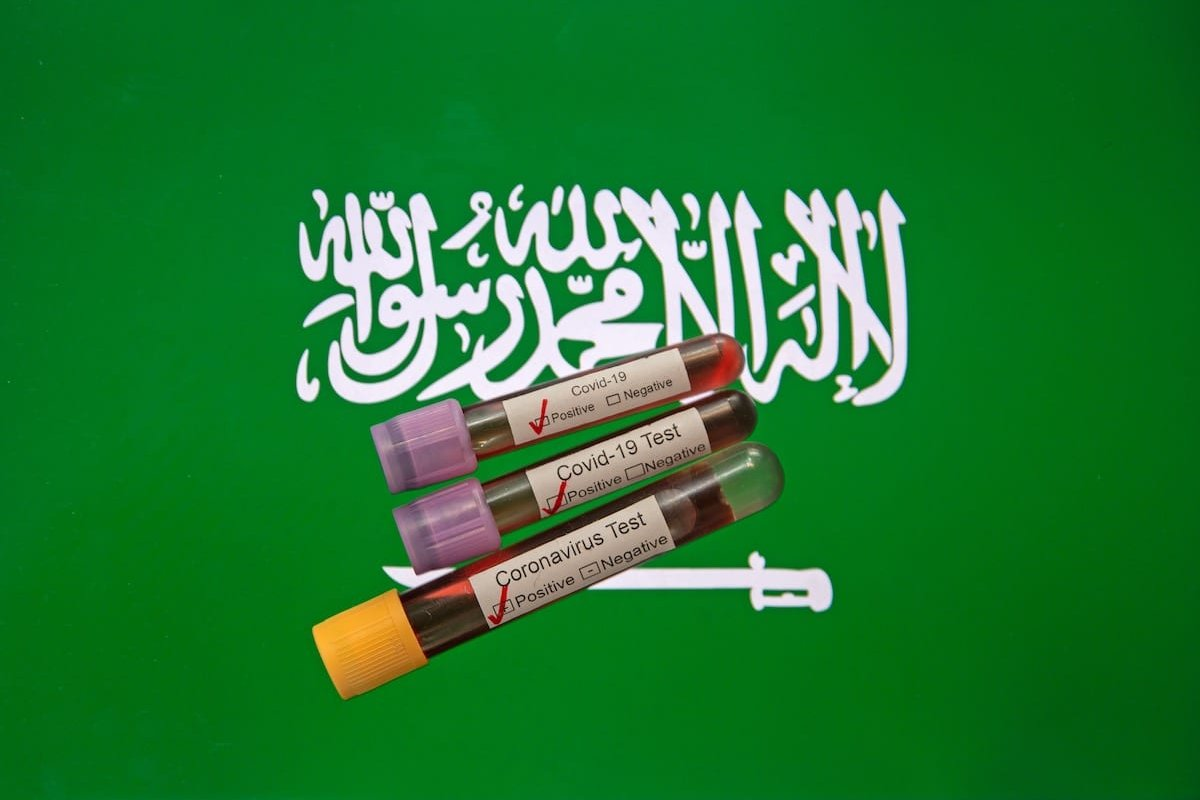 In this photo illustration coronavirus (COVID-19) positive blood samples are seen in front of a computer screen displaying the flag of Saudi Arabia [Mehmet Emin Mengüarslan - Anadolu Agency]