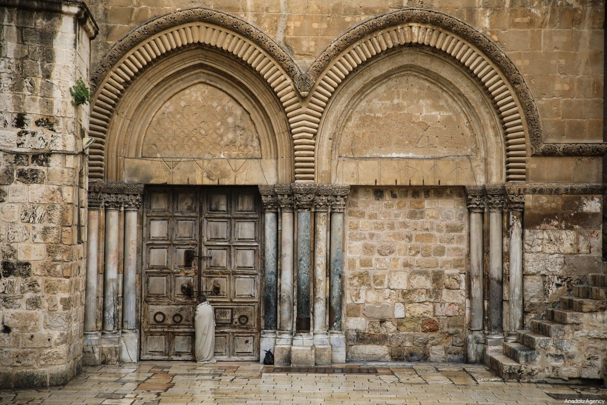 A person prays in front of the closed Church of the Holy Sepulchre on Good Friday in Jerusalem on 10 April, 2020 [Mostafa Alkharouf/Anadolu Agency]