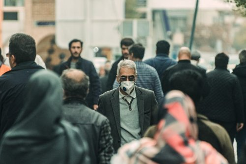 People are seen on a street after Iranian government gradually remove the precautions against the novel coronavirus (Covid-19) pandemic leading shops to re-open in Tabriz, Iran on 12 April 2020. [Stringer - Anadolu Agency]