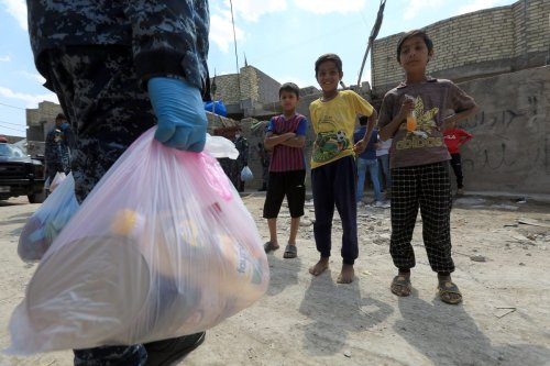 Iraqi security forces distribute food to people in need due to coronavirus (Covid-19) pandemic in Baghdad, Iraq on 13 April 2020 [Murtadha Al-Sudani - Anadolu Agency]