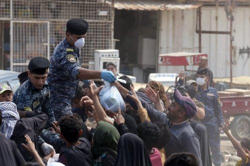 Iraqi security forces distribute food to people in need during curfew due to coronavirus (Covid-19) pandemic in Baghdad, Iraq on 13 April, 2020 [Murtadha Al-Sudani/Anadolu Agency]