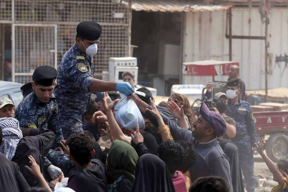 Iraqi security forces distribute food to people in need during curfew due to coronavirus (Covid-19) pandemic in Baghdad, Iraq on 13 April 2020. [Murtadha Al-Sudani - Anadolu Agency]
