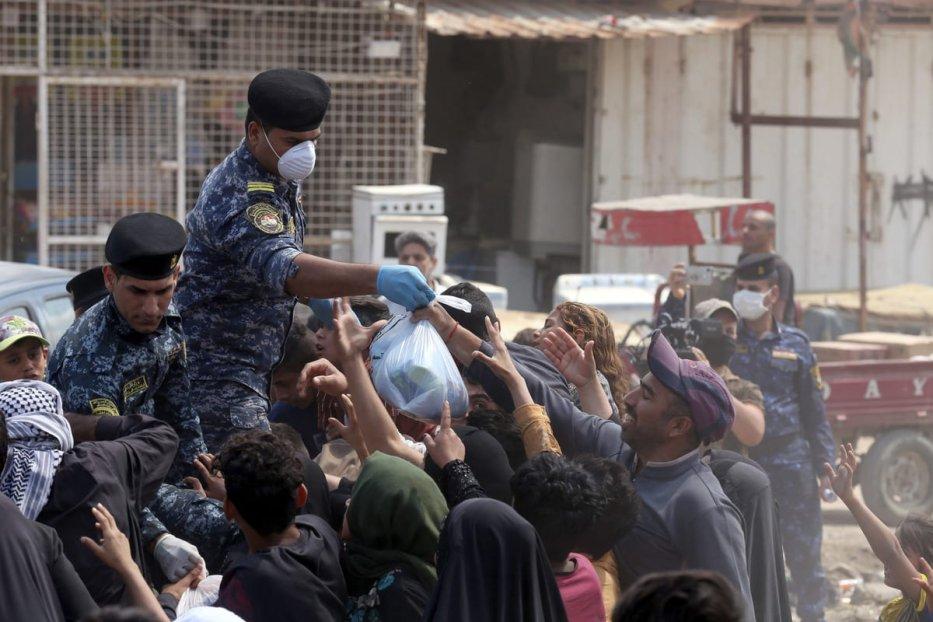 Iraqi security forces distribute food to people in need during curfew due to coronavirus (Covid-19) pandemic in Baghdad, Iraq on 13 April 2020. [Murtadha Al-Sudani - Anadolu Agency]