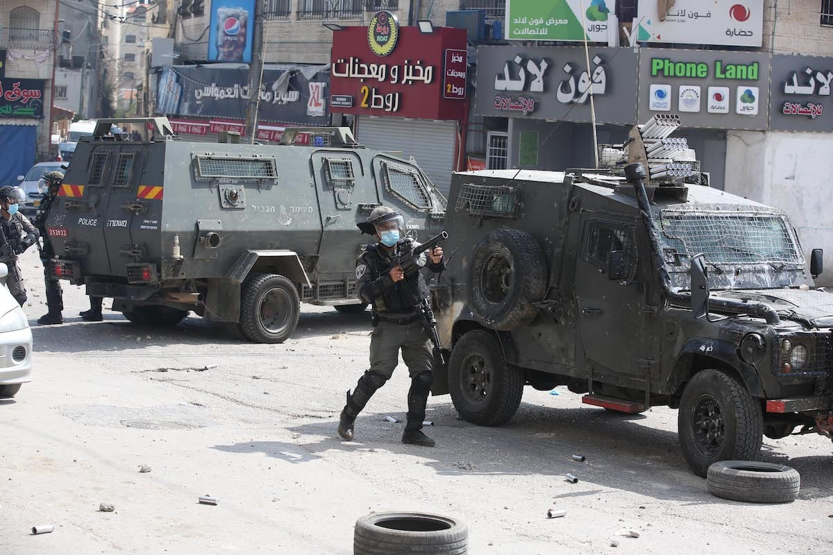 Israeli soldiers use tear gas to disperse the Palestinians reacting against the raid on Kalandia Camp in Ramallah, West Bank on April 14, 2020 [Issam Rimawi - Anadolu Agency]