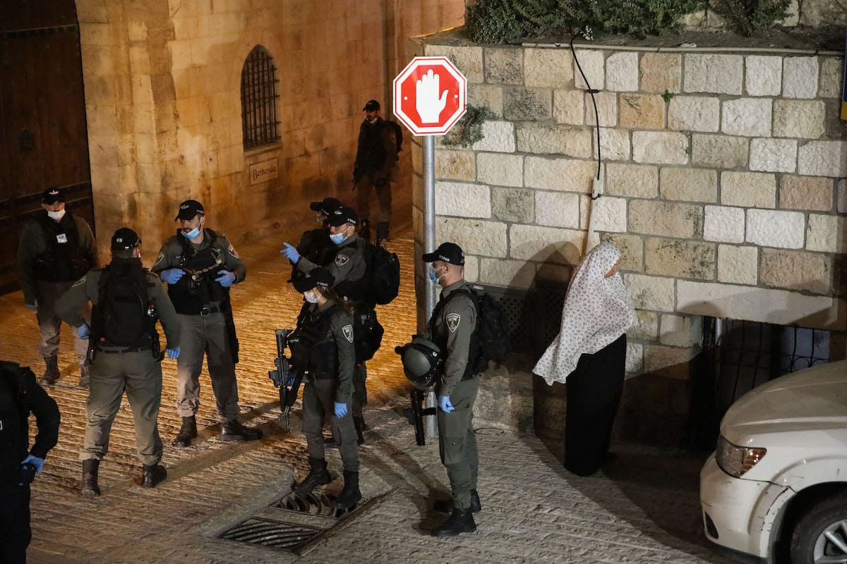 Israeli police officers stand guard as Palestinian worshippers perform the Taraweeh prayer outside the closed-down Masjid al Aqsa compound during the holy month of Ramadan at Old Town in Jerusalem on April 26, 2020 [Mostafa Alkharouf / Anadolu Agency]