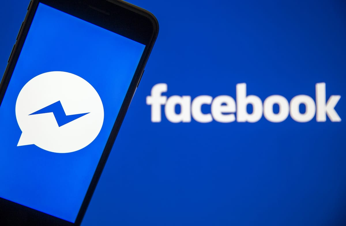 A mobile phone screen displays the Facebook Messenger logo in front of a computer screen showing the Facebook sign on 27 February, 2020 [Ali Balıkçı/Anadolu Agency]