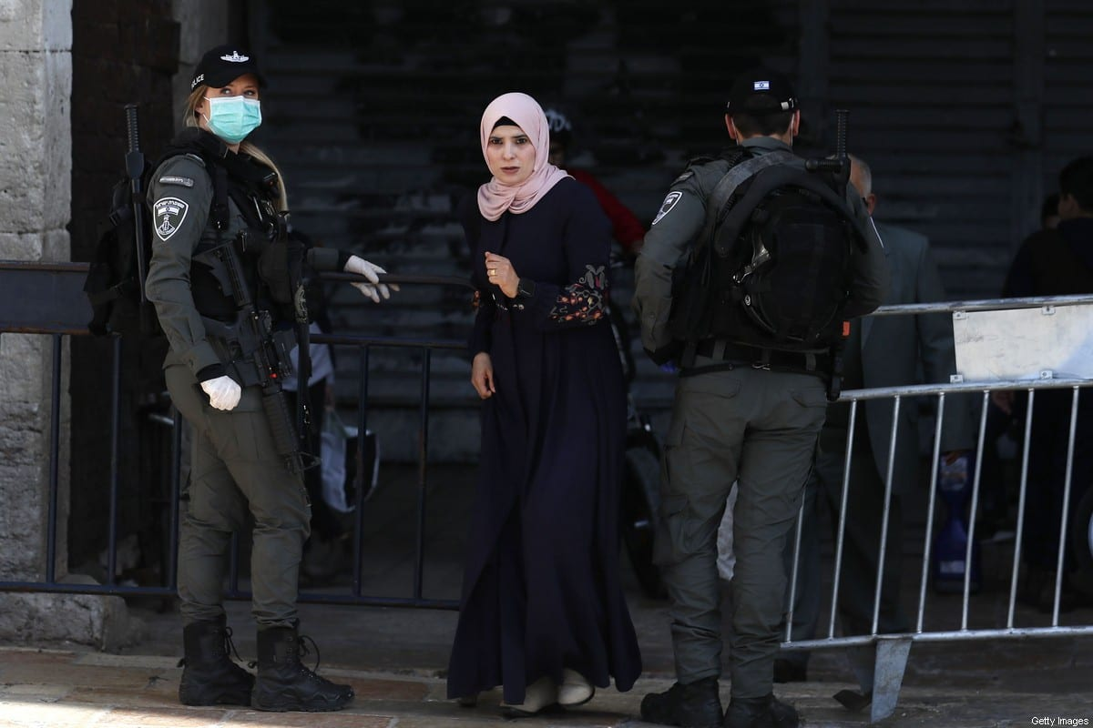 A Palestinian woman walks past Israeli border police standing guard near the Damascus Gate in Jerusalem's Old City, on March 26, 2020, during the ongoing novel coronavirus pandemic crisis. (Photo by Ahmad GHARABLI / AFP) (Photo by AHMAD GHARABLI/AFP via Getty Images)