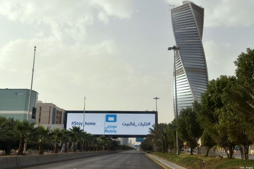 "A picture taken on March 26, 2020, shows a huge billboard which says ""Stay Home"" in the empty King Fahd main road in the Saudi capital Riyadh, after the Kingdom began implementing an 11-hour nationwide curfew, on the day of an emergency G20 videoconference, to discuss a response to the COVID-19 crisis [FAYEZ NURELDINE/AFP via Getty Images]"