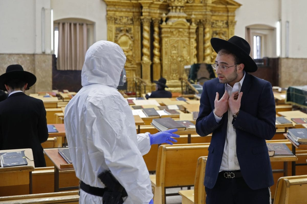 An Israeli police officer, dressed in protective outfit, speaks to a Yeshiva (Jewish educational institution for studies of traditional religious texts)student, in the Israeli city of Bnei Brak on April 2, 2020, during a control to insure that social distancing measures imposed by Israeli authorities meant to curb the spread of the novel coronavirus are being respected. [JACK GUEZ/AFP via Getty Images]