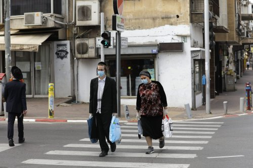 Ultra-Orthodox Jews wearing protective masks walk by carrying bags of shopping in the religious Israeli city of Bnei Brak, near Tel Aviv, on April 6, 2020, [MENAHEM KAHANA/AFP via Getty Images]