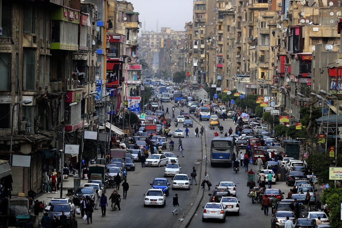 Cars and pedestrians are pictured in one Egypt's popular streets in Cairo, shortly before a curfew was imposed to contain the spread of the novel coronavirus on 25 March 2020 [KHALED DESOUKI/AFP/Getty Images]