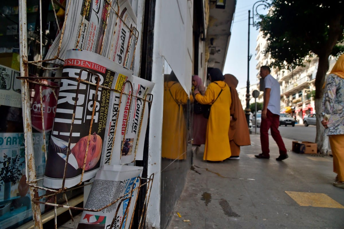 People walk past a newspaper stand in Algiers, Algeria on 16 September 2019 [RYAD KRAMDI/AFP/Getty Images]