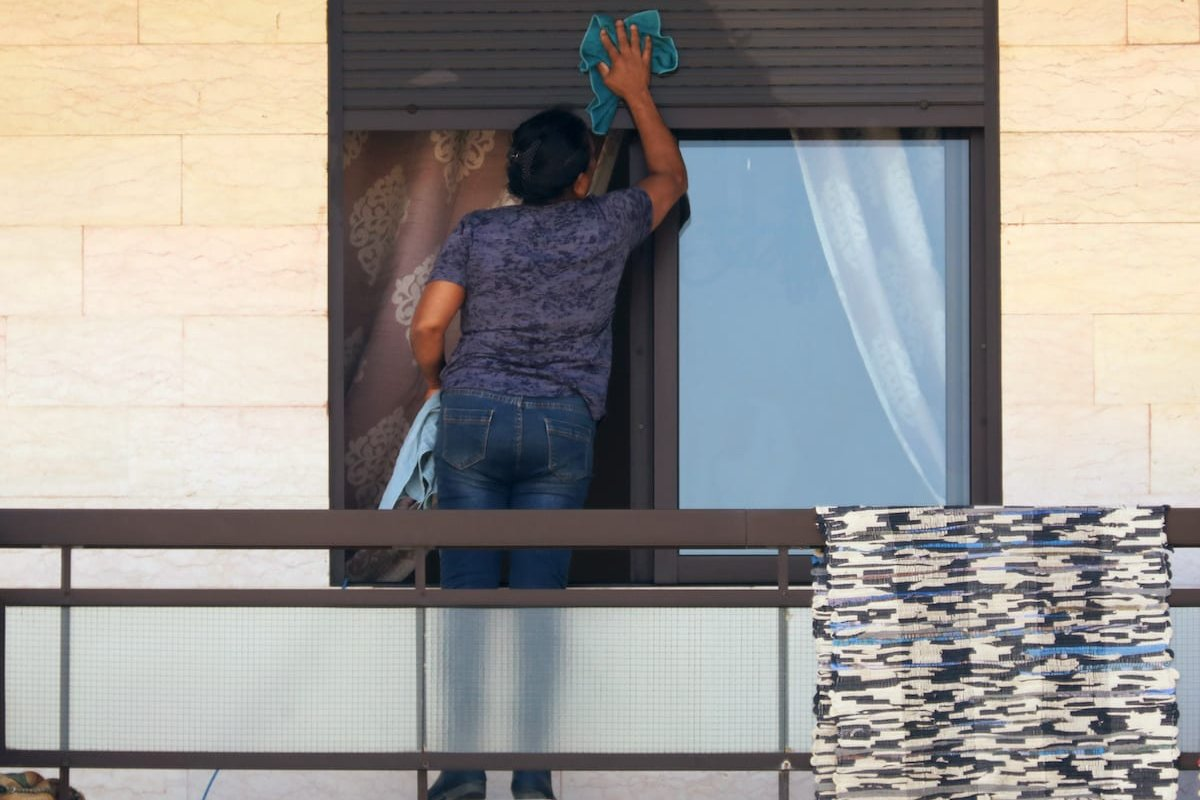 A foreign domestic worker cleans window blinds in Beirut, Lebanon, May 21, 2020. [REUTERS/Mohamed Azakir]