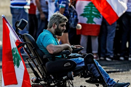 A man seated in a wheelchair with a Lebanese national flag attends a demonstration to protest against corruption in Beirut, on 22 October 2019 [JOSEPH EID/AFP/Getty Images]