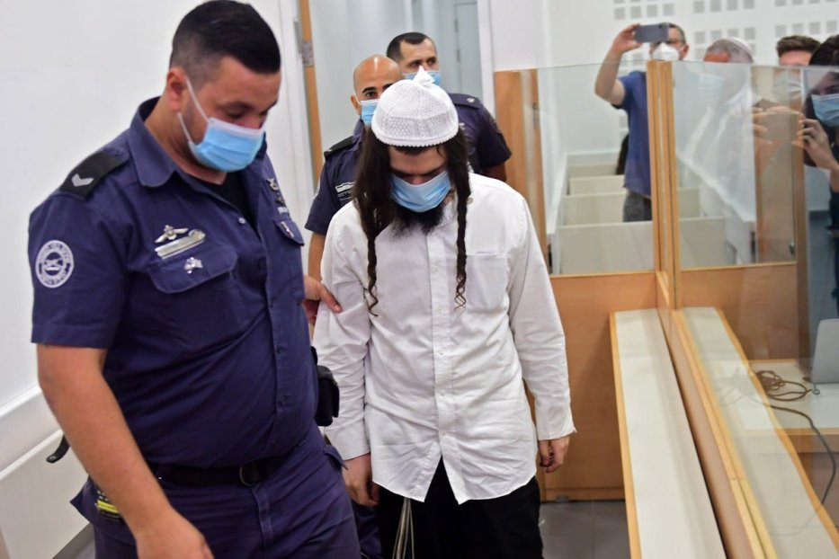 Amiram Ben-Uliel, a Jewish settler, is lead by police for his sentencing hearing over the 2015 arson attack that killed a Palestinian toddler and his parents [AVSHALOM SASSONI/POOL/AFP/Getty Images]