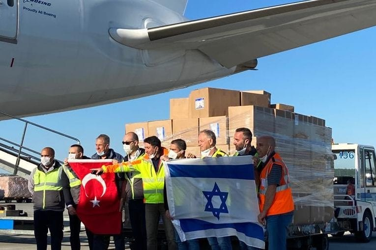 An image showing Turkish and Israeli flags being held up, purportedly while an El Al Israel Airlines starts cargo flight is being loaded, uploaded on May 24, 2020 [RoeyGilad / Twitter]