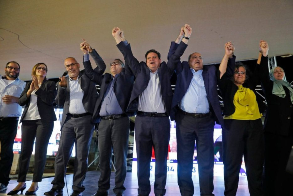 (L to R) Ofer Cassif, Jewish member and candidate for the Hadash (Democratic Front for Peace and Equality) party that is part of the Joint List alliance, applauds with Heba Yazbak, member and candidate for the Balad (National Democratic Alliance) party as Osama Saadi, member and candidate for the Arab Movement for Change (Taal) party raises his hands together with Balad party member and candidate Mtanes Shehadeh, Hadash's chairman and candidate Ayman Odeh, Taal's leader and candidate Ahmad Tibi, Hadash's member and candidate Aida Touma, and the Islamic Movement's member and candidate Iman Khatib Yassin before supporters at the alliance's campaign headquarters in the northern Israeli city of Nazareth on September 17, 2019 [AHMAD GHARABLI/AFP via Getty Images]