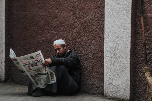 A man reads a newspaper on a sidewalk in Cairo on 15 December 2019 [MOHAMED EL-SHAHED/AFP/Getty Images]