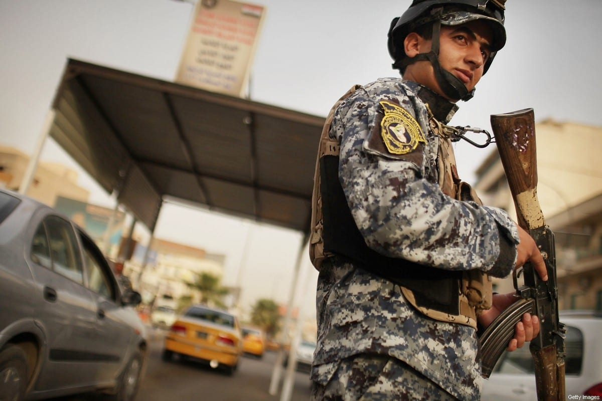 An Iraqi police officer watches cars at a checkpoint on July 20, 2011 in Baghdad, Iraq [Spencer Platt/Getty Images]