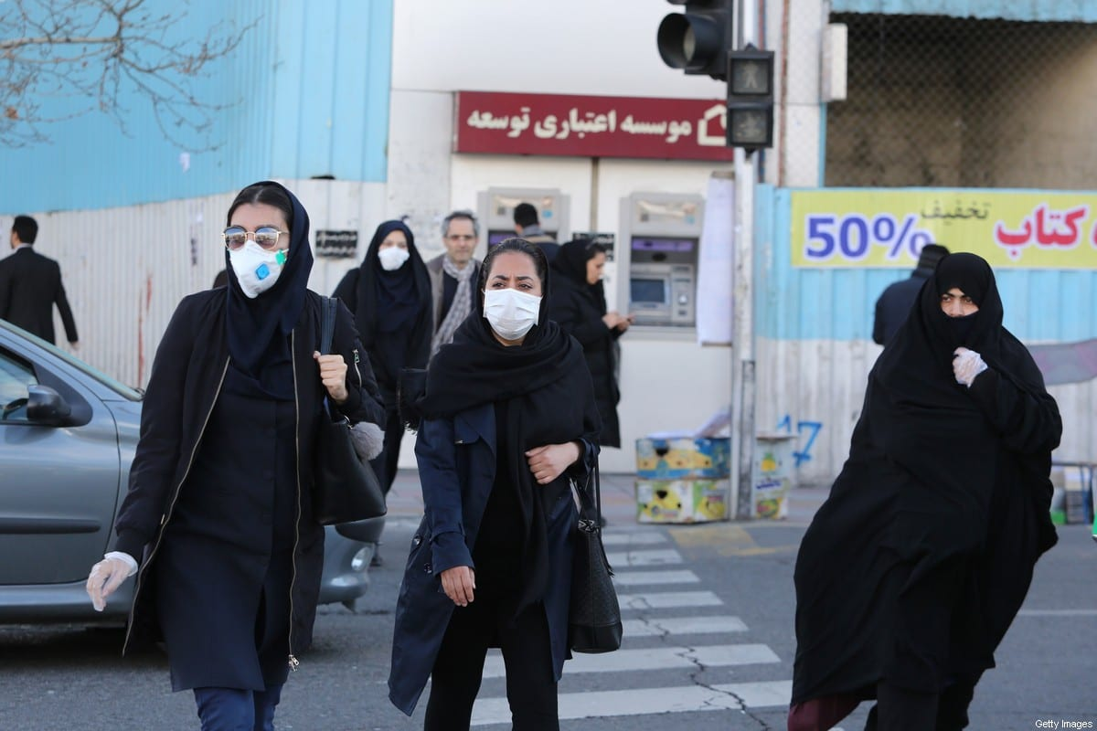 Women wearing protective masks cross a street in the Iranian capital Tehran on March 2, 2020 [ATTA KENARE/AFP via Getty Images]