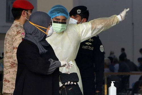 Kuwaiti healthy ministry workers prepare to scan expatriates living in Kuwait who returned from Egypt, Syria and Lebanon, as they arrive to a specified place to be tested for coronavirus in Kuwait City on 12 March 2020. [YASSER AL-ZAYYAT/AFP via Getty Images]