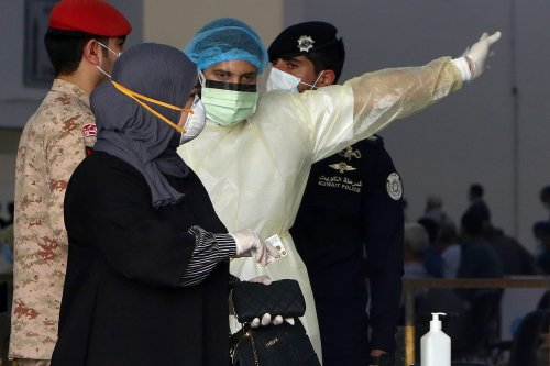 Kuwaiti healthy ministry workers prepare to scan expatriates living in Kuwait who returned from Egypt, Syria and Lebanon, as they arrive to a specified place to be tested for coronavirus in Kuwait City on March 12, 2020 [YASSER AL-ZAYYAT/AFP via Getty Images]