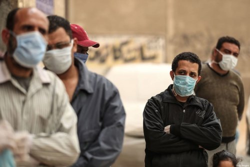Egyptian men wearing masks wait outside a centre of non-governmental organisation Egyptian Food Bank to receive cartons with foodstuffs on April 05, 2020 [MOHAMED EL-SHAHED/AFP via Getty Images]