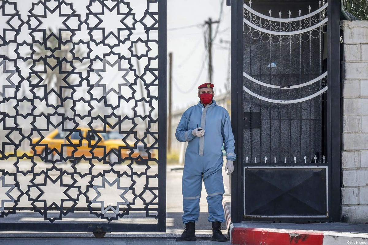 A member of the security wearing personal protective equipment as a precaution against the coronavirus waits at the Rafah border crossing with Egypt, in the southern Gaza Strip on April 13, 2020 [SAID KHATIB/AFP via Getty Images]