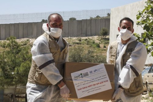 Members of the French Action Against Hunger NGO distribute hygiene and sanitation products to Palestinian residents of al-Ramadin village amid the coronavirus (COVID-19) pandemic, southwest of the West Bank town of Hebron on 13 April, 2020 [HAZEM BADER/AFP via Getty Images]