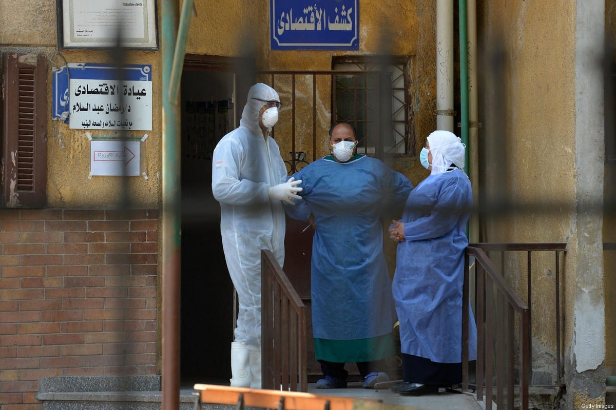 Members of the medical staff at the infectious diseases unit of the Imbaba hospital in the capital Cairo, gather for a break on 19 April,2020 [AHMED HASAN/AFP via Getty Images]