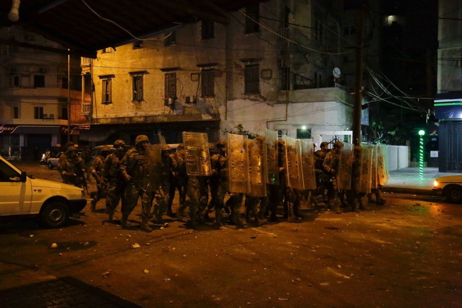 Lebanese army soldiers advance as protesters throw stones amid overnight confrontations in Lebanon's northern city of Tripoli on April 28, 2020, [IBRAHIM CHALHOUB/AFP via Getty Images]