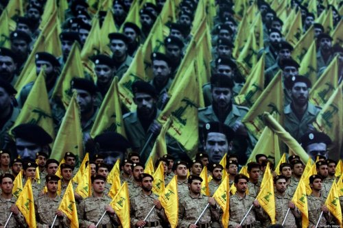 Members of Hezbollah's armed wing stand to attention as hundreds of people gather to watch a televised speech by Hassan Nasrallah on February 22, 2008, in Beirut, Lebanon. [JOSEPH BARRAK/AFP via Getty Images]