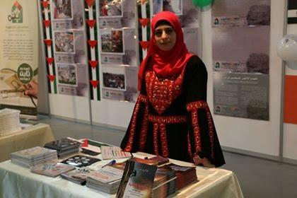 Asma at an exhibition highlighting the Palestinian cause, wearing a traditionally embroidered dress. Her grandfather, Fayez Al-Saadi, is pictured right.[Middle East Monitor]