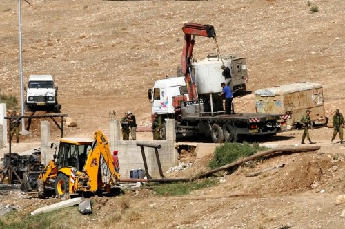 Israeli soldiers surround a bulldozer as it destroys a Palestinian water well in the West Bank [Wagdi Eshtayah/ApaImages]
