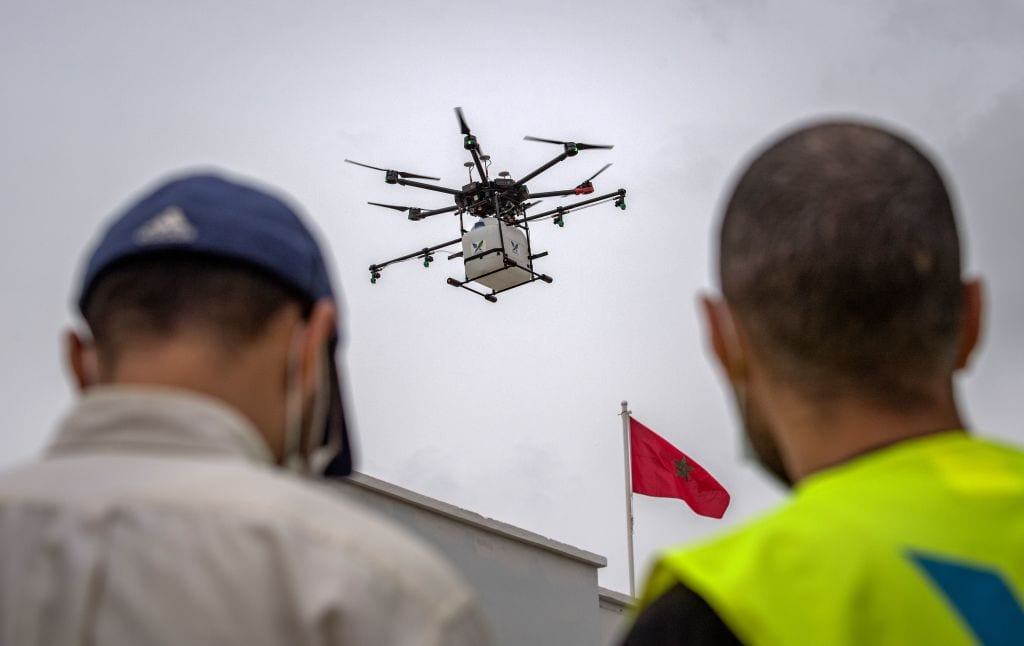 An employee of a Moroccan startup company pilots a drone equipped with disinfectant liquid, in a street of Harhoura near the capital Rabat on 23 April, 2020 [FADEL SENNA/AFP via Getty Images]