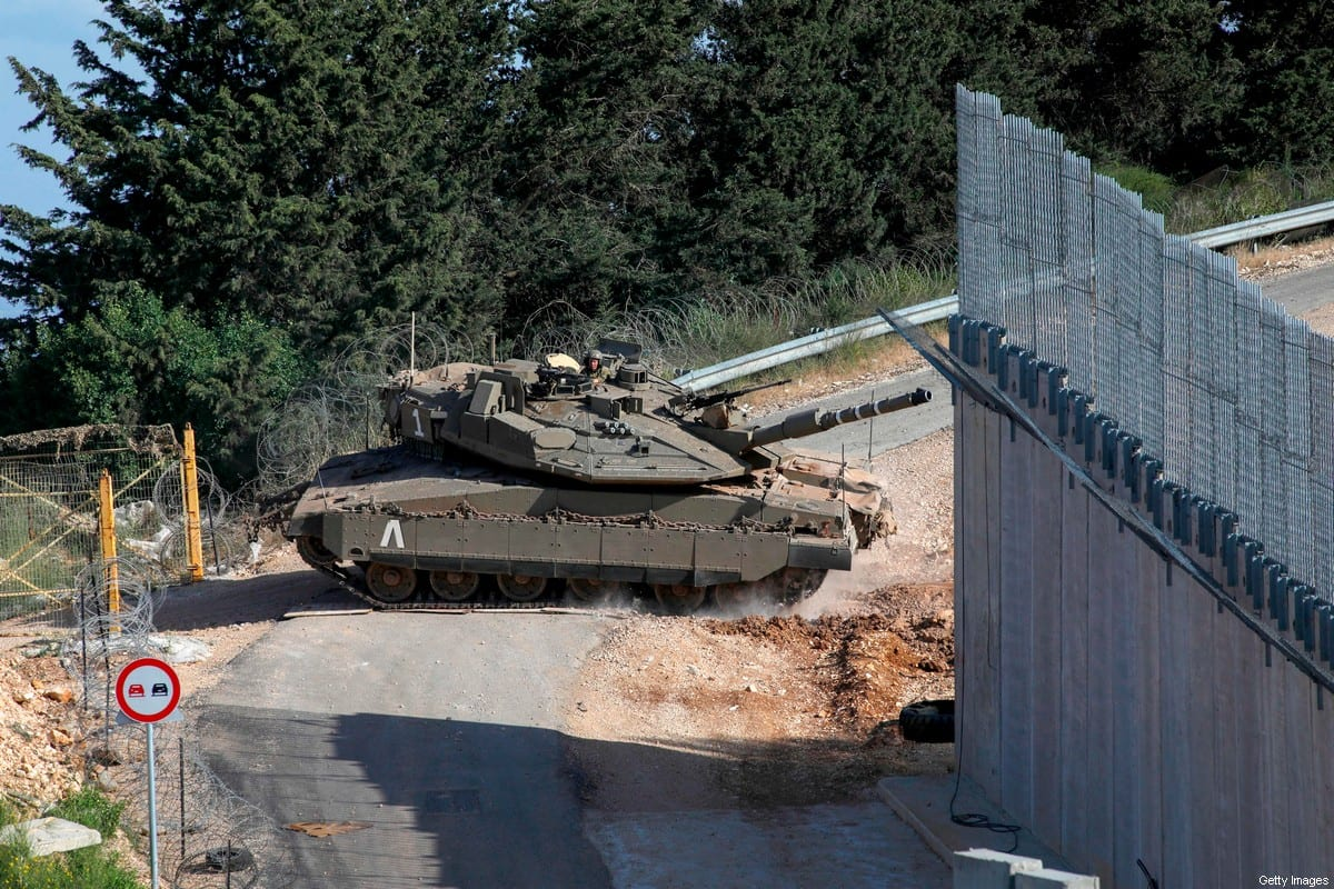 """This picture taken on June 2, 2020, near the northern Israeli kibbutz of Misgav Am, shows Israeli army Merkava IV battle tank taking part in routine manuevers near the """"blue line"""", a demarcation line drawn by the UN to mark Israel's withdrawal from southern Lebanon in 2000, close the Lebanese village of Adaisseh. [JALAA MAREY/AFP via Getty Images]"""