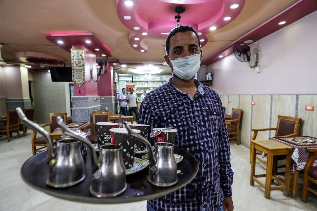 A waiter carries an order at a cafe in the Egyptian capital Cairo on 27 June 2020, after authorities relaxed the lockdown measures in place to curb the spread of coronavirus. - A night-time curfew was imposed in late March restricting movement from 8 pm to 6 am, but it has been eased in recent weeks. Prime Minister Mostafa Madbouli said cafes and restaurants will restart operations at a reduced capacity of 25 percent in the first phase of relaxing the lockdown. [MOHAMED EL-SHAHED/AFP via Getty Images]