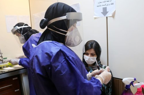 An official of Keyvan Virology Laboratory takes a sample from a woman as people arrive to have Covid-19 test due to rises in coronavirus cases in Tehran, Iran on July 14, 2020. [Fatemeh Bahrami - Anadolu Agency]