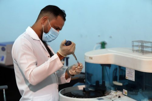 A health official works on a sample in International Fair ground in Baghdad, Iraq on 18 July, 2020 [Murtadha Al-Sudani/Anadolu Agency]