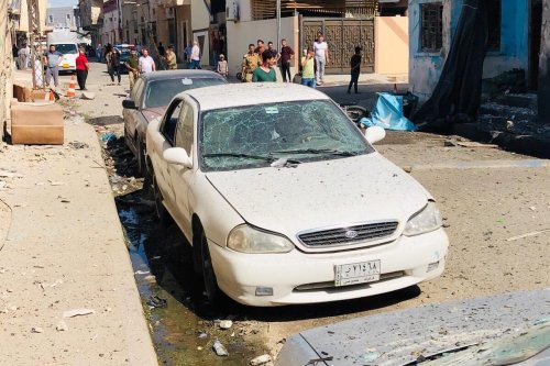 Damaged cars are seen as people inspect the damaged building, belonging to Badr Brigade backed up by Hasdi Sabi forces closely related to Iran after the bomb attack in Kirkuk, Iraq on 20 July 2020. One injury was reported. [Ali Makram Ghareeb - Anadolu Agency]