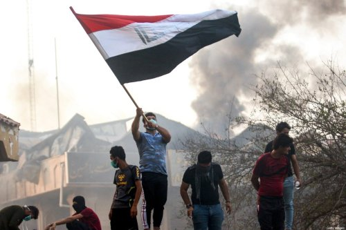 An Iraqi protester waves a national flag while demonstrating outside the burnt-down local government headquarters in the southern city of Basra on September 7, 2018 during demonstrations over poor public services. [HAIDAR MOHAMMED ALI/AFP via Getty Images]