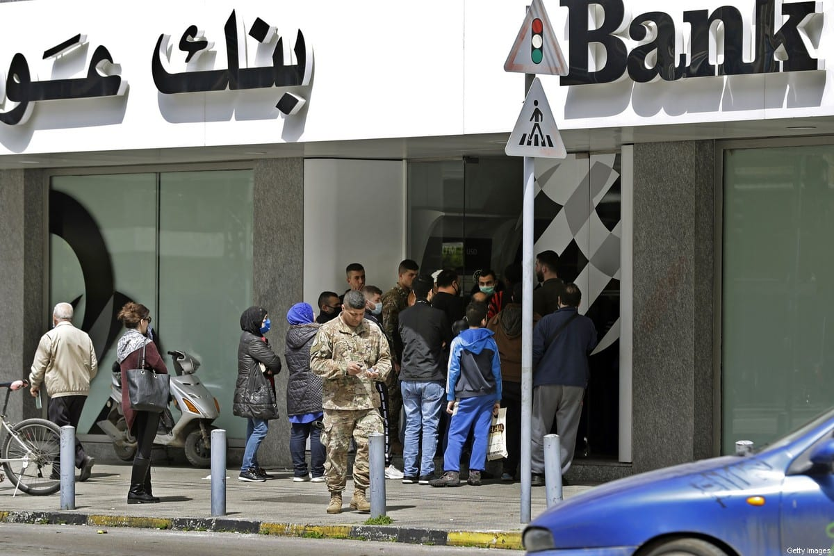 Lebanese wait outside a bank to retrieve their salaries on March 31, 2020 in the northern coastal city of Tripoli in Lebanon [JOSEPH EID/AFP via Getty Images]