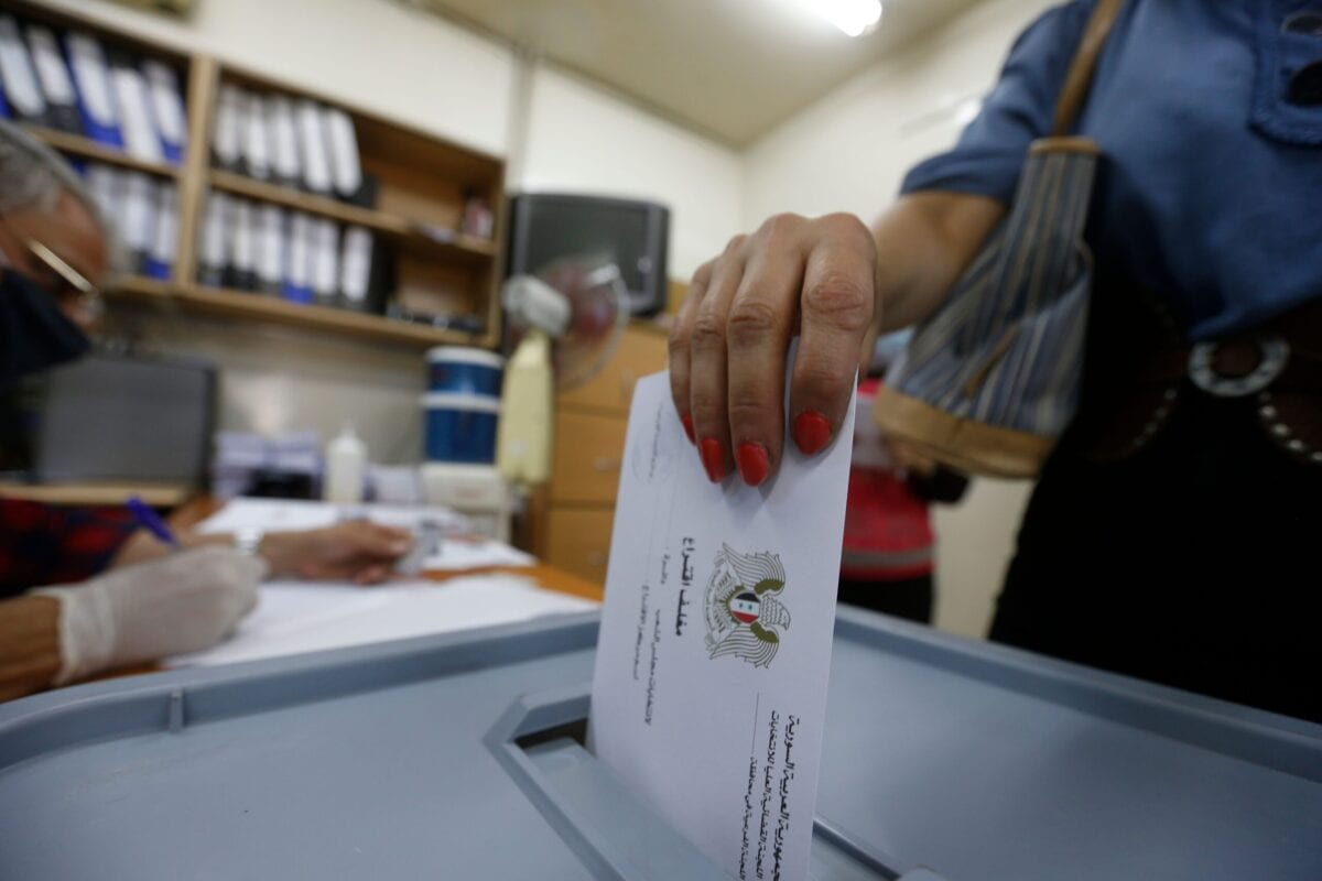 A woman casts her ballot at a polling station in the Syrian capital Damascus on July 19, 2020, during the parliamentary elections [LOUAI BESHARA/AFP via Getty Images]