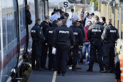 Danish police guards a train with migrants, mainly from Syria and Iraq, at Rodby railway station, southern Denmark, on September 9, 2015 [JENS NOERGAARD LARSEN/AFP via Getty Images]