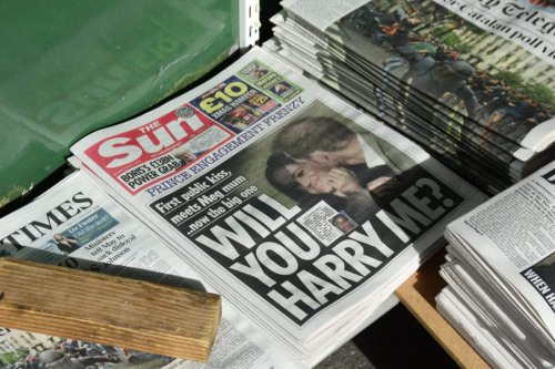 A variety of daily newspapers, including The Sun, for sale at a newstand in London, England [Robert Alexander/Getty Images]
