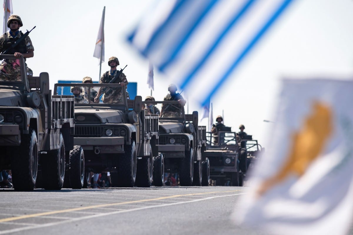 Greek (C) and Cypriot (R) national flags wave at military trucks in Nicosia on 1 October 2019 [IAKOVOS HATZISTAVROU/AFP/Getty Images]