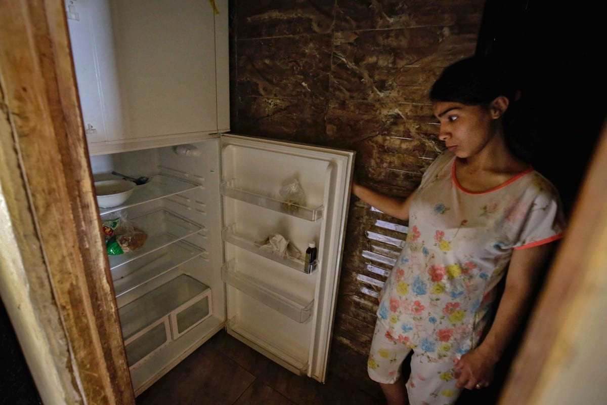 A Lebanese woman stands next to her empty refrigerator in her apartment in Beirut, Lebanon on 17 June 2020 [IBRAHIM CHALHOUB/AFP/Getty Images]